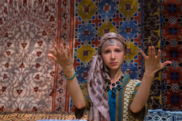 Muslim girl in national dress sitting near the beautiful carpets
