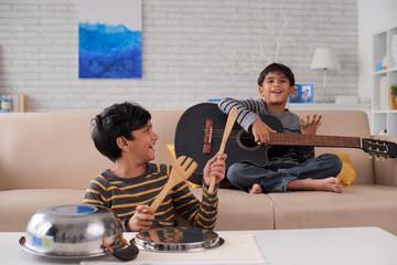 Indian kids enjoying playing instruments at home