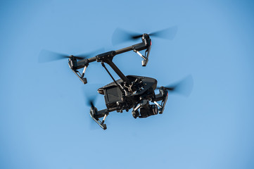 Drone flying in the sky/Drone-quadrocopter with camera hovers on the blue sky