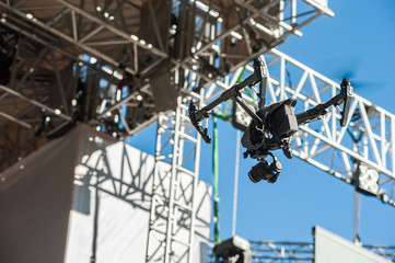 Вrone on stage background/Drone with camera hovers over the stage during a concert