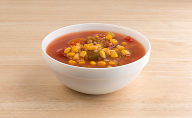 Corn okra and tomatoes stew in a white bowl on a wood table.