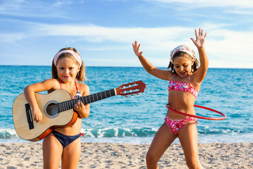 Kids dancing and singing with guitar on beach.