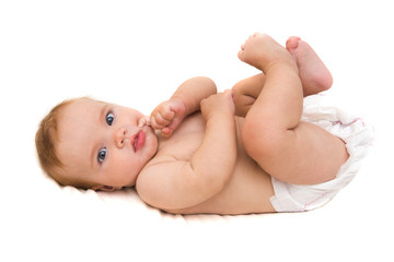 Funny little baby lying down on a blanket . Newborn child relaxing in bed. Nursery for young children. Textile and bedding for kids.