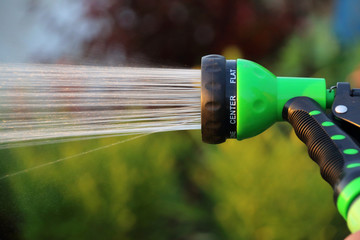 Watering flower bed with an adjustable shower (spray) in the summer evening garden