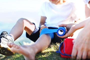 Obraz Bandażowanie nogi. Matka opatruje dziecięce kolano bandażem elastycznym. - fototapety do salonu