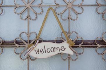welcome sign hanging in a door