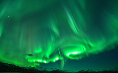 Spectacular auroral at night display over mountain,Iceland
