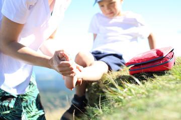 Obraz Dziecko skręciło nogę w kostce podczas górskiej wycieczki. Opatrywanie złamanej nogi. - fototapety do salonu