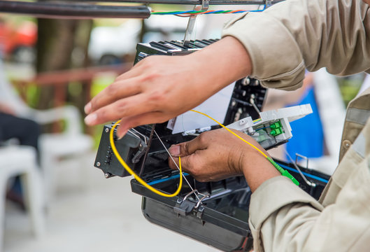 Technicians are install cabinet on fiber optic cable.Blur images