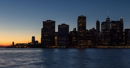 Wall Mural - New York City skyscrapers between sunset and dusk with city lights. Time lapse cityscape view of Lower Manhattan Financial District and East River