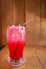 Red soda water on wood background