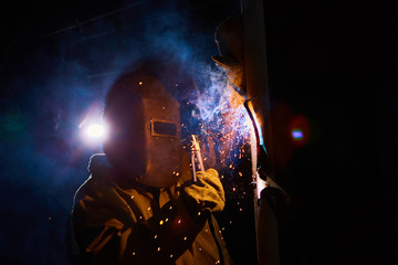 welder worker welding metal by electrode
