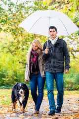 Poster Camping Woman and man having walk with dog in autumn rain