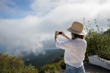 tourist taking photo in mountain by phone