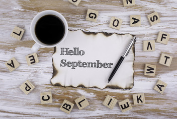 On the table a piece of paper and text - Hello September