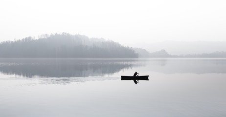 Autumn. Fog over the lake. Silhouette of mountains in the background. The man floats in a boat with a paddle.