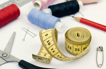 sewing spools, scissors and tape measure on white cloth