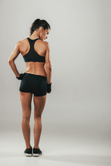 Back side view of woman in sports shorts and top