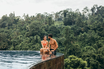 Couple sitting in infinity pool in tropical resort