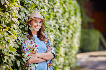 Portrait of beautiful woman standing near hedge
