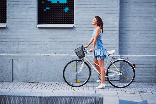 Happy woman with bike standing agains brick building