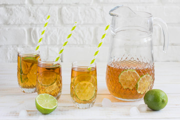 Ice tea in a glass with a slice of lime. White wooden plank back
