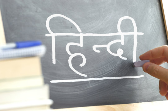 Hand writing on a blackboard in a Hindi class. Some books and school materials.