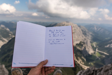 Making an entry into the summit booklet on Lampsenspitze in Tyrol Austria