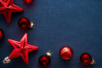 Red christmas decorations (stars and balls) on dark blue canvas background. Merry christmas card. Winter holidays. Xmas theme. Happy New Year.