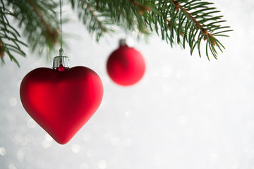 Red christmas ornaments (heart and ball) on the xmas tree on glitter bokeh background. Winter holiday theme.