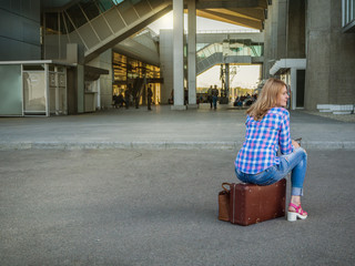 Girl sitting on a vintage retro suitcase at the airport. Concept