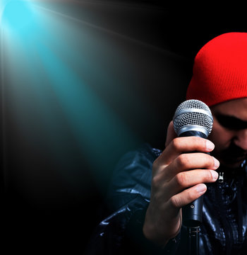 asian male singer singing in concert with spotlight background