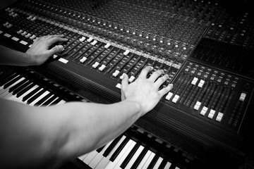 sound engineer hands on mixer & electric piano, synthesizer in home studio