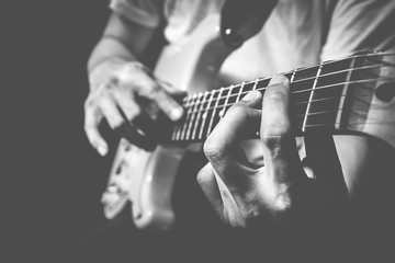 closeup male musician hands playing electric guitar on stage + bw film filter