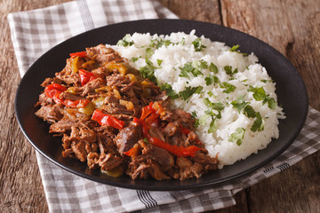 Mexican food ropa vieja: beef stew in tomato sauce with vegetables and rice. Horizontal