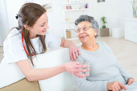 Doctor giving old lady a glass of water