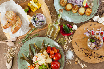 Other meat, fish, cheese dishes and appetizers with herbs, spices, oil and wine on a wooden background