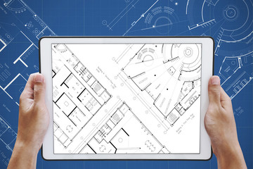 Hand holding digital tablet with architectural planning on screen, and architectural blueprint background
