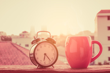 The joy of the day,Alarm clock with a red cup of coffee on the terrace with the morning light.