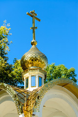 Golden dome of the church with a cross on the sky background