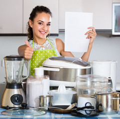 Positive housewife with  appliances  in domestic kitchen