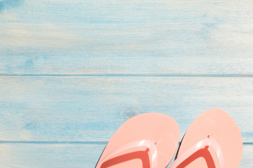 pink flip flops on blue wooden table with sunlight