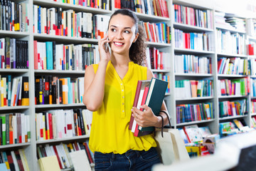 Smiling  woman chatting on mobile phone and taking  books