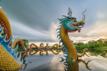 Colorful dragons statue with goddess  + reflection on water surface and beautifully blue sky at twilight time