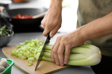 Male hands cutting celery on wooden board closeup