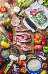Ingredients for cooking dinner. Raw uncooked lamb meat chops, rice, oil, spices and vegetables over wooden background, top view