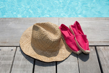 Summer background with hat shoes on the wooden deck and pool