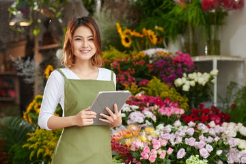 Portrait of pretty Asian florist with tablet computer in hands