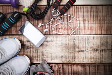 Wall Mural - Sports equipment - sneakers, skipping rope, dumbbells, smartphone and headphones. Sport background on wooden floor, top view.