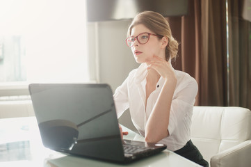 Portrait of young woman in red glasses. She sits in the office and working at a computer. The sunlight in the window